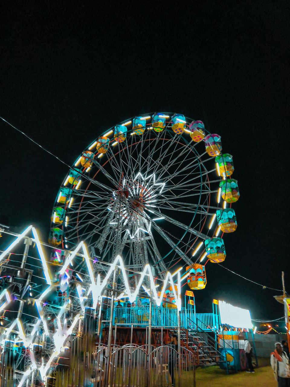 LOW ANGLE VIEW OF ILLUMINATED FERRIS WHEEL AGAINST SKY