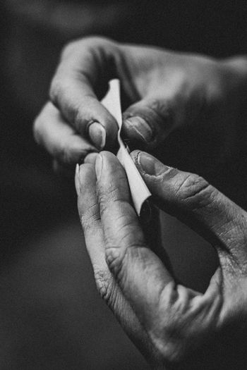 Close-up of cropped hands holding marijuana joint