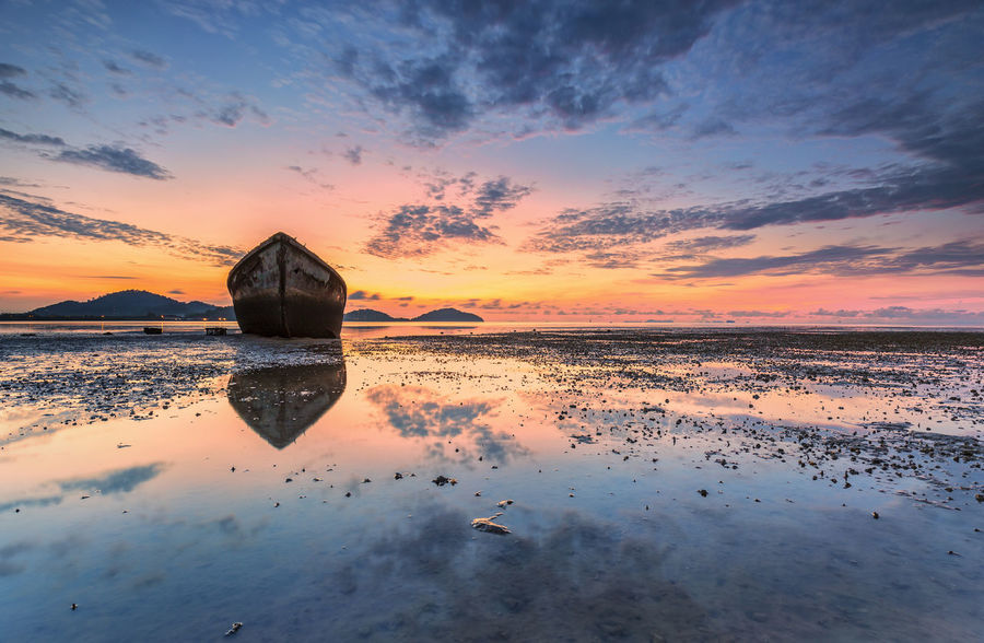 Red WreckedShip Beach Beauty In Nature Boat Cloud - Sky Nature Orange Color Scenics - Nature Sea Sky Sunset Tranquil Scene Tranquility Water Wrecked Boat.