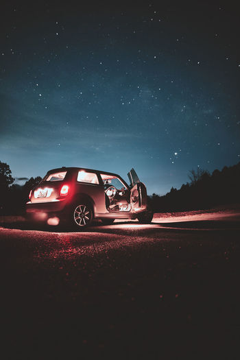 Car on road against sky at night