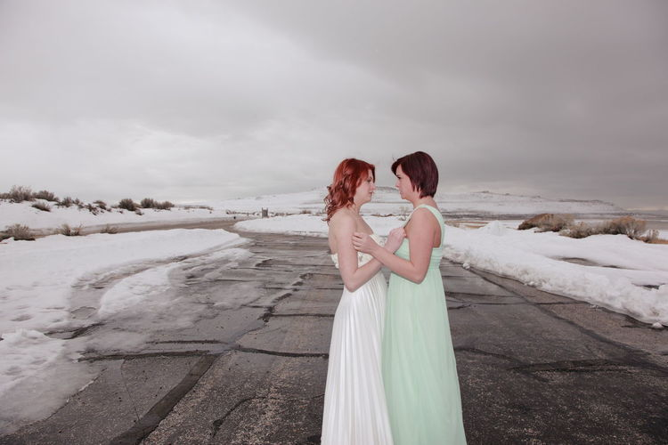 Sisters Looking Each Other While Standing On Road Against Cloudy Sky During Winter