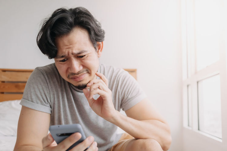 Midsection of man using mobile phone at home
