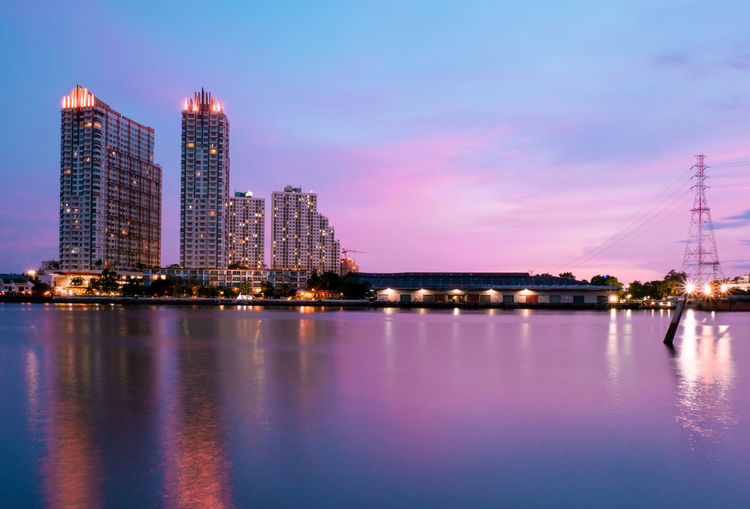 Illuminated city by river against sky at dusk