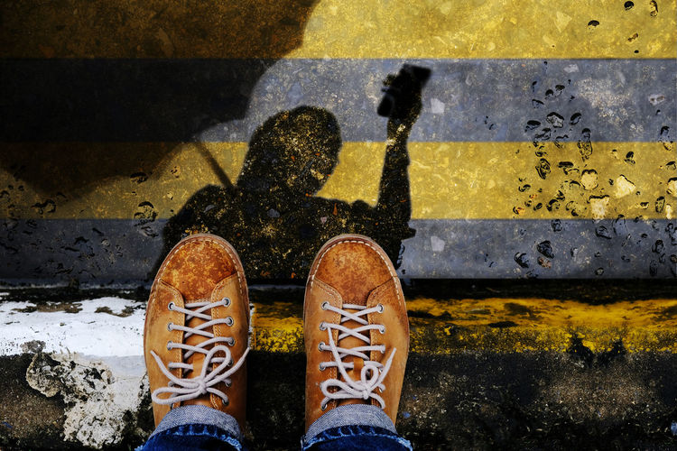 Low Section Of Person Wearing Shoes Standing On Wet Road