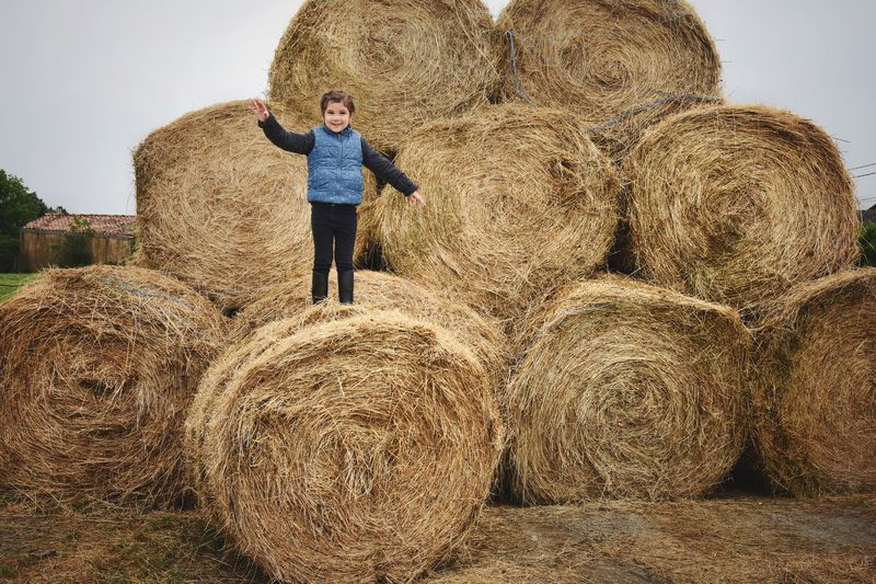Full length of man with hay bales on field