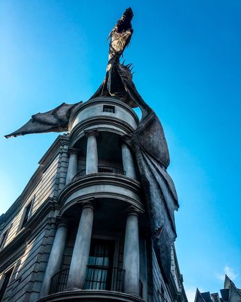Statue Architecture Low Angle View Built Structure Building Exterior Sculpture Human Representation Day Outdoors Sky No People History Travel Destinations Blue Clear Sky Dragon Florida Orlando Universal Studios
