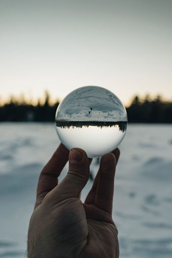 Close-up of hand holding crystal ball against snow
