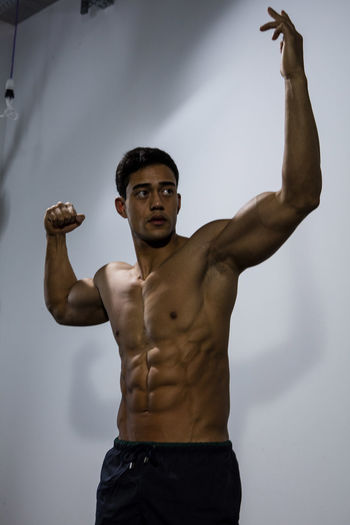 Muscular male fitness model posing behind a grey wall. Medium shot. Adult Asian  Athlete Body & Fitness Human Body Man Nam Vo Shirtless Sportsman Arms Raised Biceps Fitness Model Grey Wall Handsome Hunk Looking Away From Camera Male Medium Shot Muscle Muscular Build One Person Strong Studio Shot Torso Upper Body