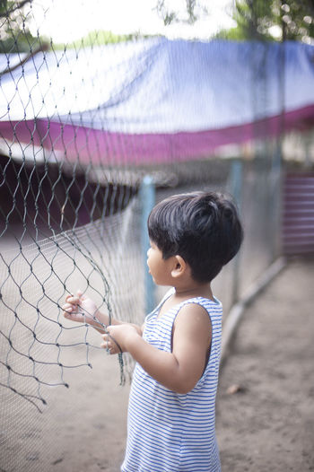 Boy standing by chainlink fence