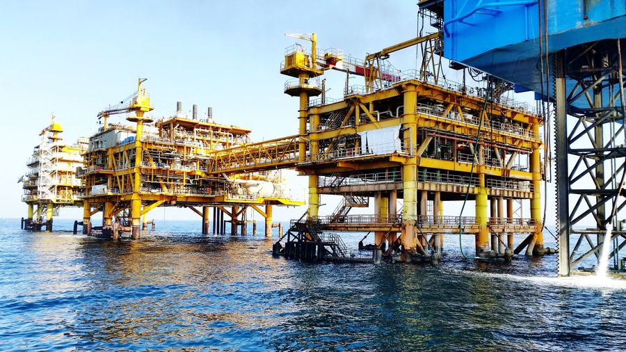 Drilling rigs in sea against sky