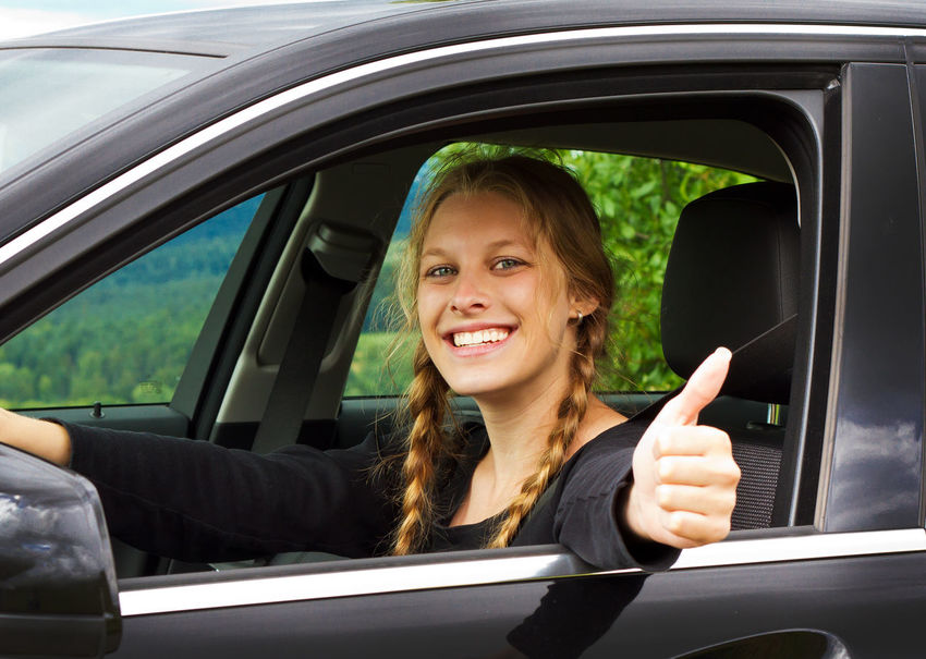 Driver Examination Happy Sitting Woman Car Cheerful Driver License Driving Ecology Envrionment Girl Happiness Land Vehicle Looking At Camera New Car People Portrait Smiling Success Successful Thumbs Up Transportation Vehicle Young Adult