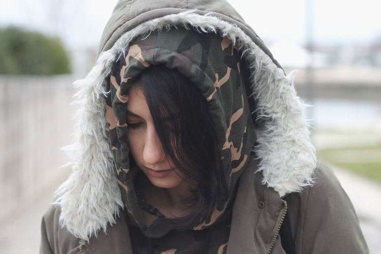 Close-Up Of Young Woman Wearing Hooded Jacket In City