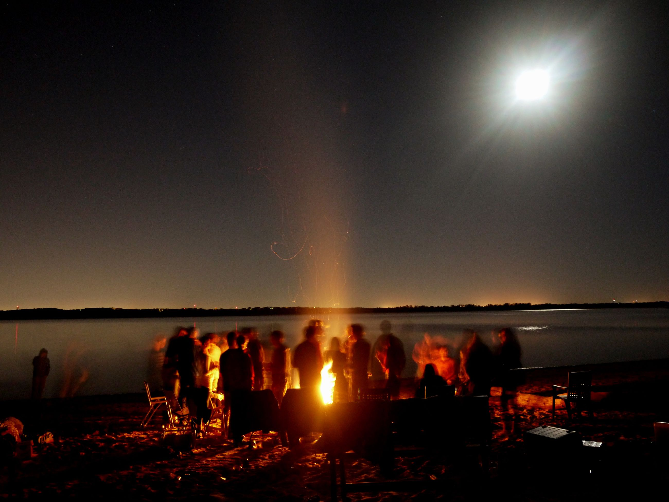 large group of people, illuminated, night, lifestyles, leisure activity, men, standing, person, water, clear sky, copy space, togetherness, burning, sky, crowd, outdoors, enjoyment, flame, celebration