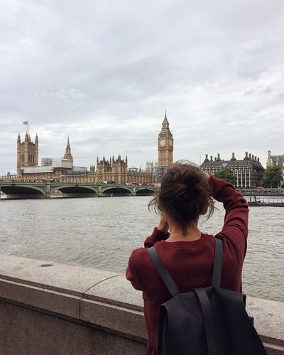 Rear view of woman looking at big ben against cloudy sky