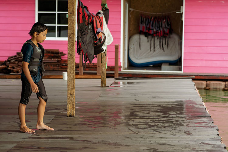 Side view of girl walking with life jacket on floor by lake