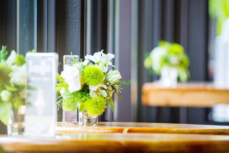 Close-Up Of White Flowers In Vase On Wooden Table