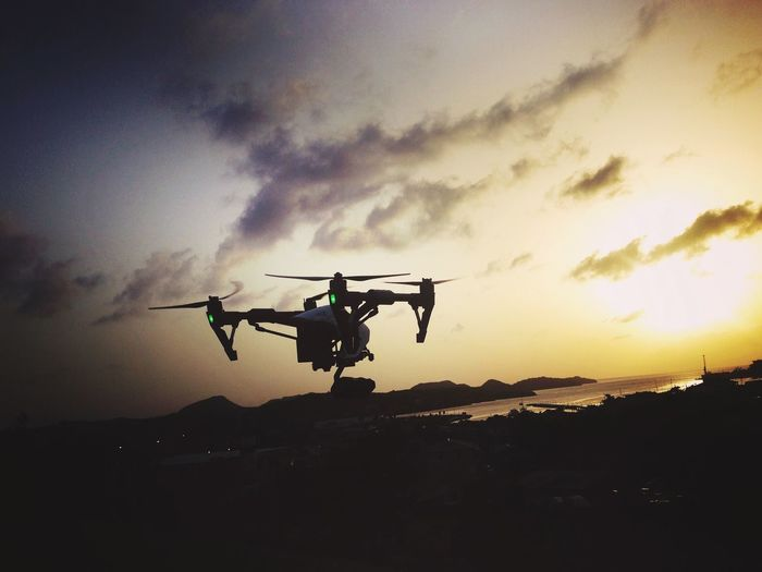 Low Angle View Of Drone Flying Against Sky During Sunset