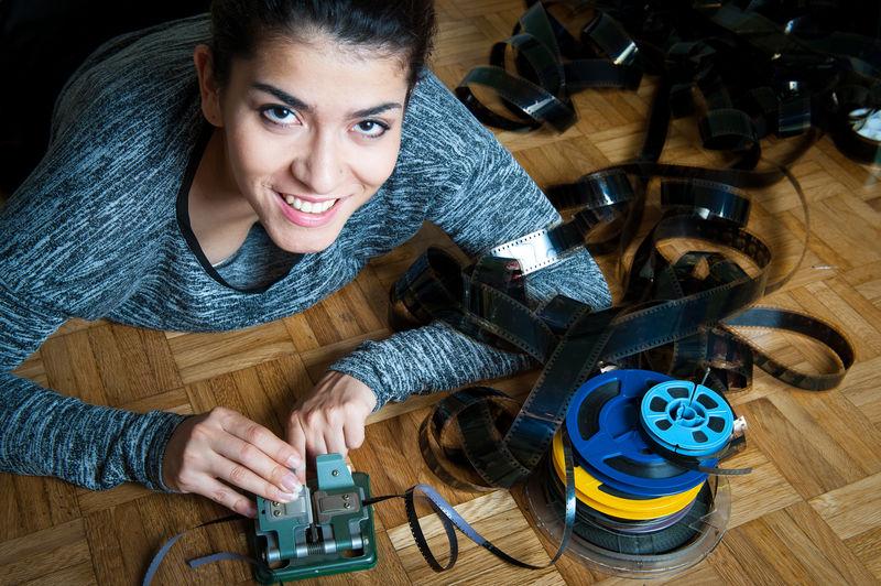 Portrait of woman repairing equipment on floor at home