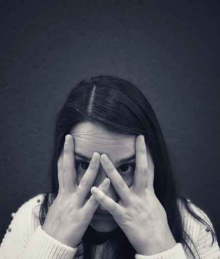 Portrait of beautiful young woman with hands covering eyes against wall
