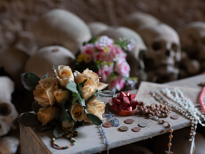 Close-up of rose bouquet on table against human skull