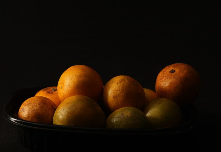 Close-up of fruits in bowl against black background