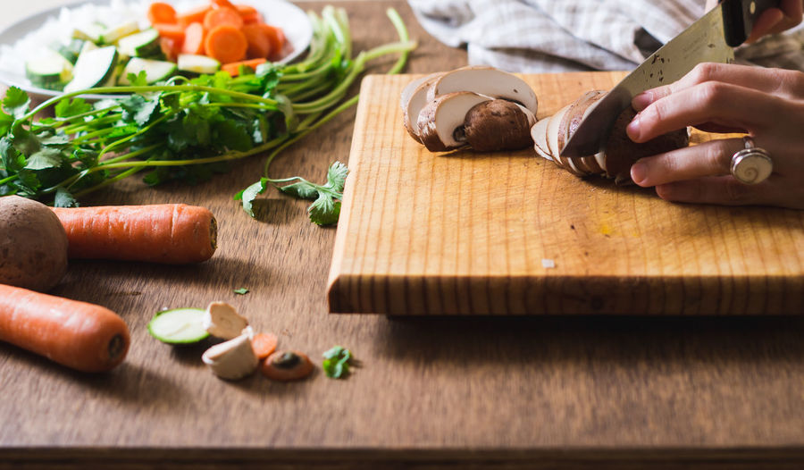 Cropped Image Of Person Chopping Mushroom On Cutting Board