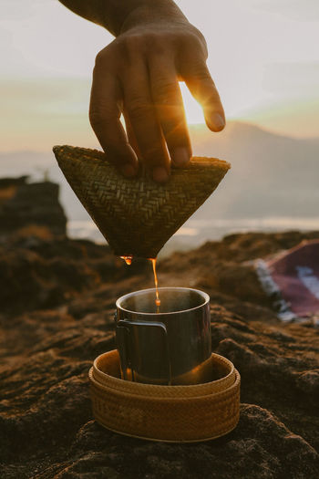 Close-up of hand holding coffee light against sky during sunrise