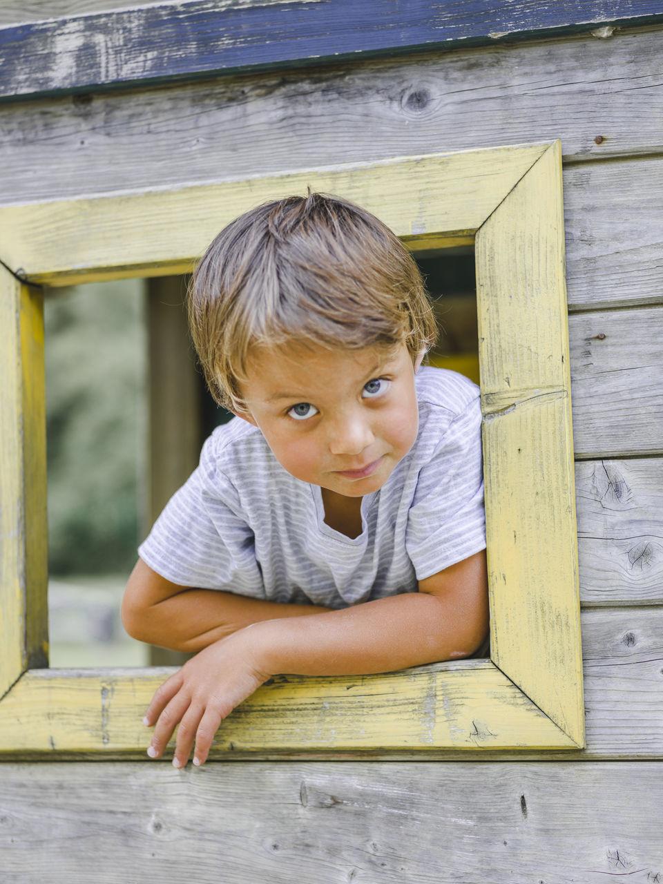 Portrait Of Boy At Wooden Window