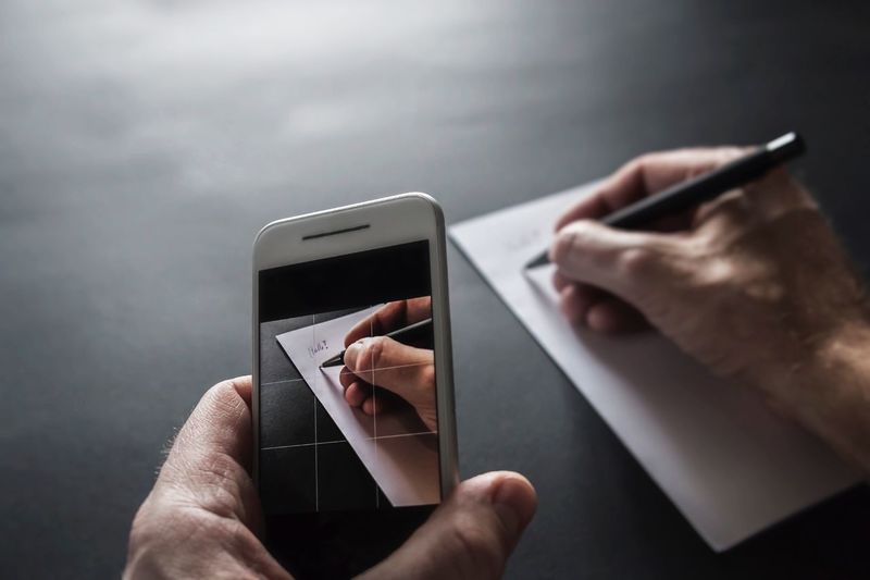 Cropped image of man photographing through smart phone while writing on paper at table