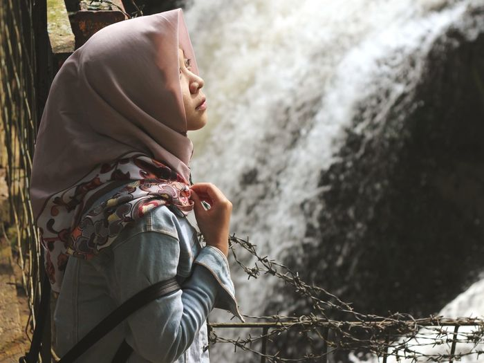 Side view of woman wearing hijab standing against waterfall