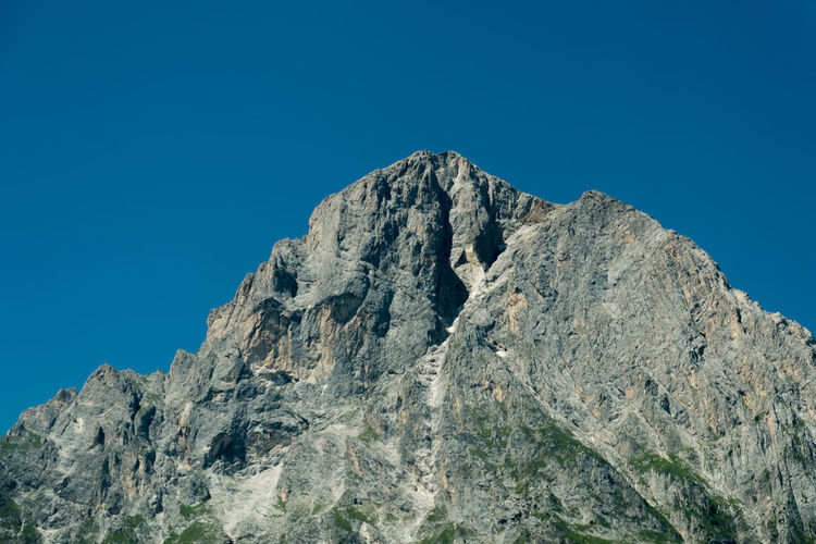 Low angle view of rock formation gransasso against clear blue sky of italy