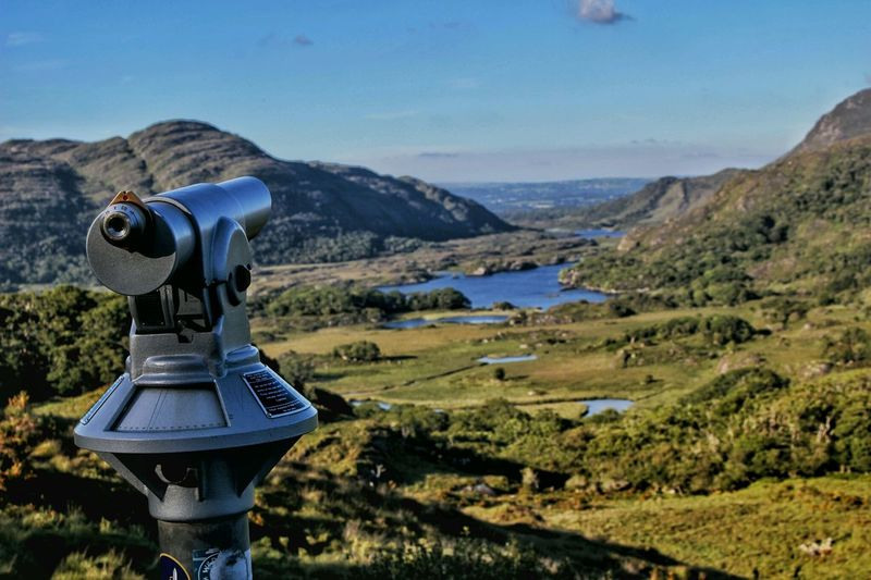 Coin Operated Binoculars Against River And Mountain