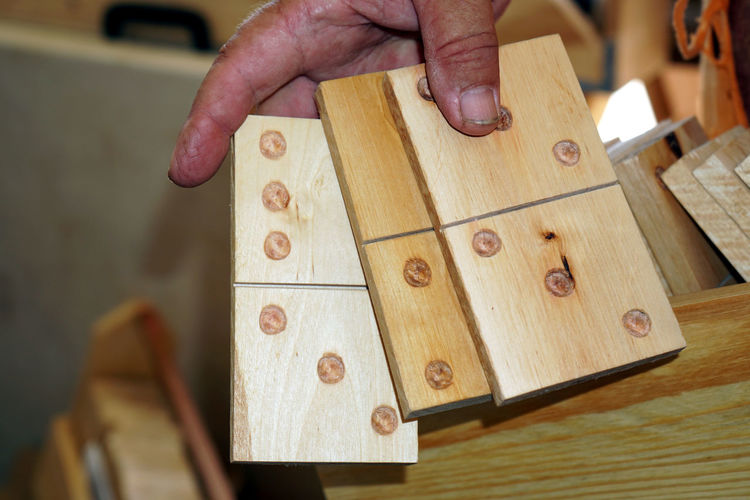Close-up of man holding wooden dominoes