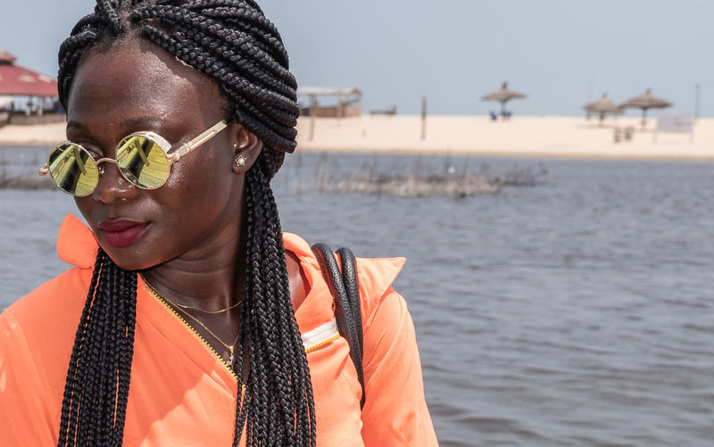 Africa woman with round sunglasses is waiting for a boat in sunny ghana