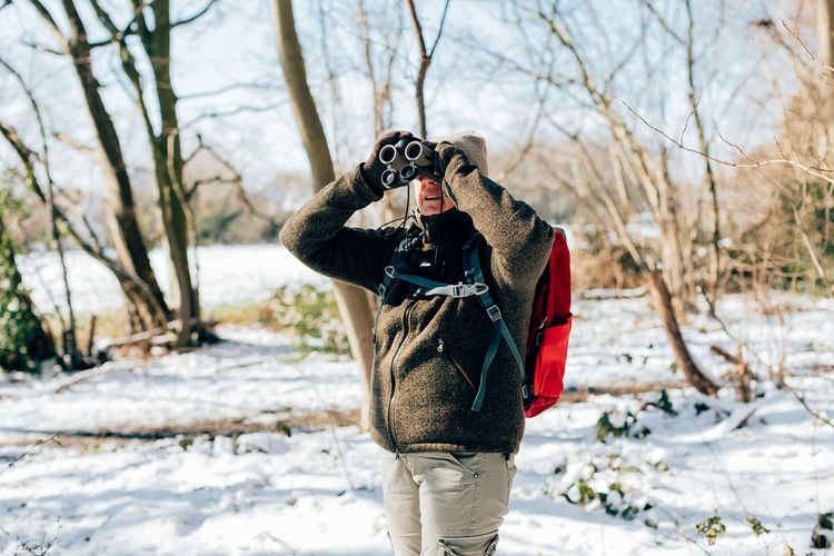 Man photographing with snow standing against trees