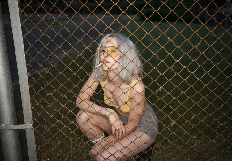 Woman smoking cigarette seen through chainlink fence