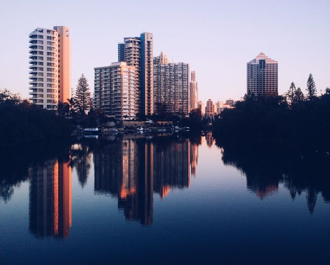 Reflection of trees and buildings in lake against sky in city