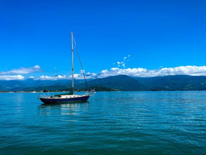 Sailboat on sea against blue sky