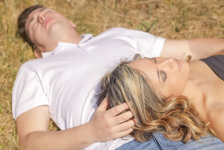Midsection of woman lying down friends relaxing outdoors