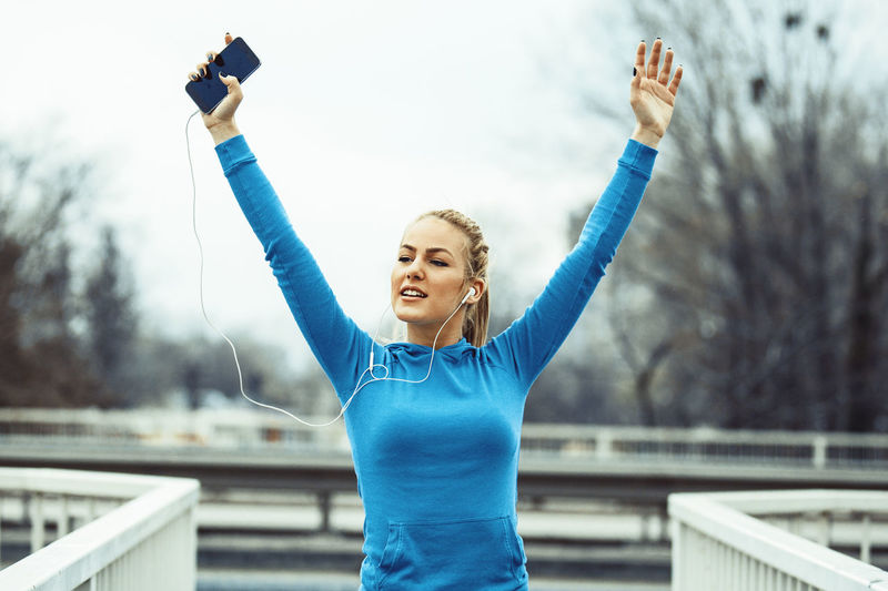 Woman listening music while exercising on footpath