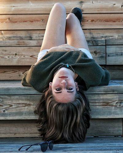 Portrait of happy woman lying on wood