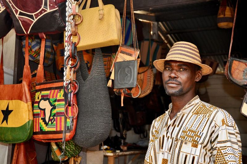 Developing Country Earn A Living Clothing Portrait One Person Hat Men Adult Africa Faces Of Africa African Ghana Market Vendor Cheerfully Straw Hat Market Retail  Standing Traditional Clothing Front View Focus On Foreground Leather Craft Leather Bags Market Stall