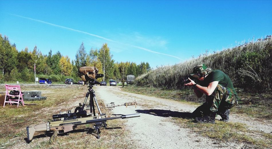 Soldier photographing rifles against sky