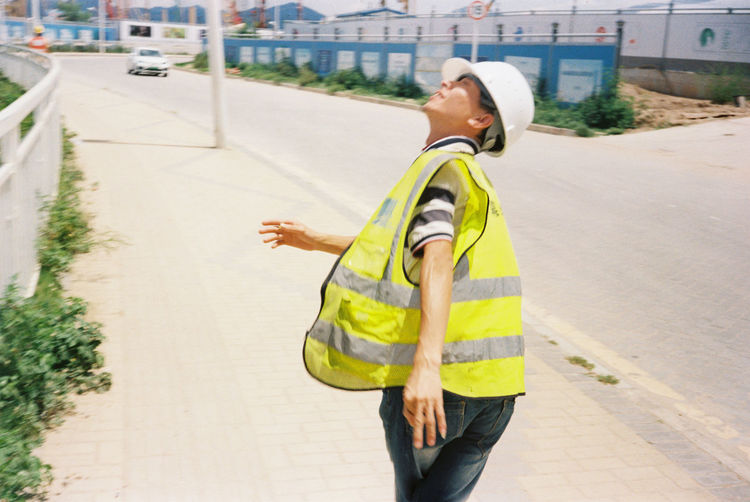 Side view of man standing on footpath