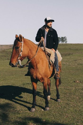Man riding horse on land against clear sky