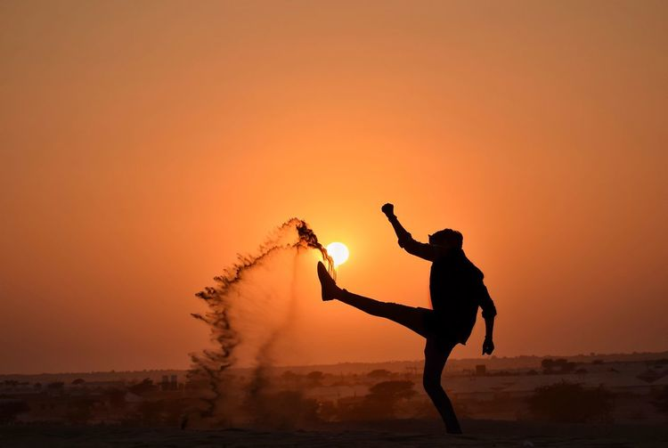 Fun with dust.! Human Sunset Sun Sunlight And Shadow Sunlight Sunset Silhouette Motion Full Length Standing Sky Sand Dune Desert Dust Splashing High-speed Photography Capture Tomorrow EyeEmNewHere