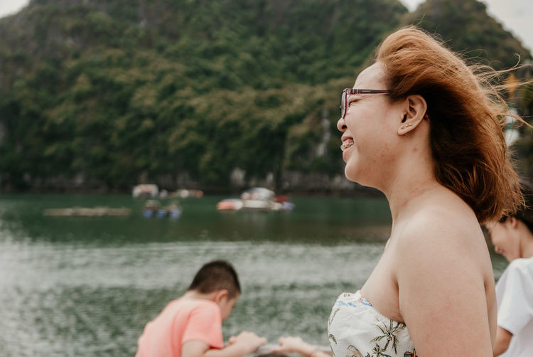 Side view of smiling young woman standing by lake against mountain