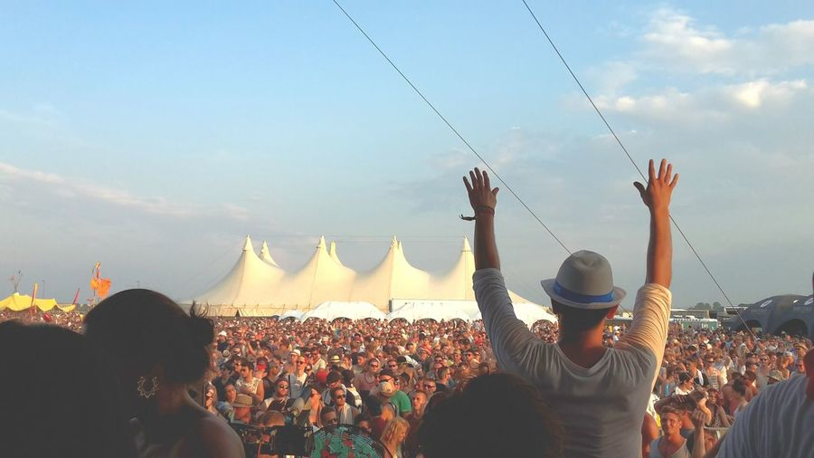 Rear View Of Man Gesturing Crowd Against Sky
