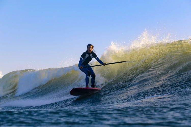 Full length of man surfing on sea against clear sky
