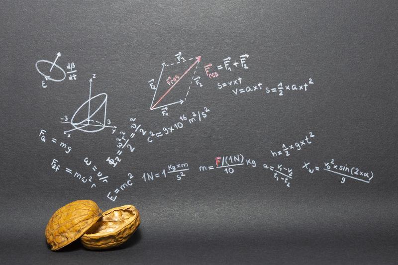 Close-up of walnut against formulas on blackboard
